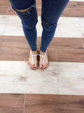 Close up of Bare Feet with Red Nail in Sandals and Blue Jeans Woman On The Tile Background. Great For Any Use Royalty Free Stock Images