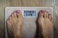 Close up of bare female feet standing on bathroom scale with written words Fitness time on display. Concept of shaping and stock photography