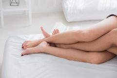 Close up barefoot legs of lesbian couple lovers sleep on white b stock photos