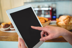 Close-up of barista finger scrolling tablet pc at cafe Stock Photography