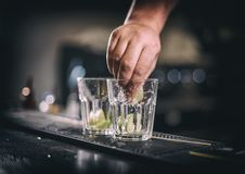 Barman hand squeezes lime juice royalty free stock image