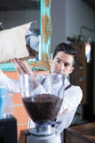 Close-up of bartender filling up  machine with coffee beans Royalty Free Stock Photos