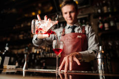 Close up bartender pouring bright red alcohol cocktail into fancy glass Royalty Free Stock Photo