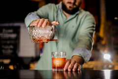 Close up bartender pouring cocktail into fancy glass Stock Images