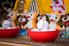Close-up of baseball balls for the game of throw at jars in a fair. In the background the jars and the prize puppets.  royalty free stock photography