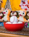 Close-up of baseball balls for the game of throw at jars in a fair. In the background the jars and the prize puppets.  stock photo