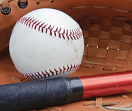 Close up of baseball in catcher's mittt with bat Royalty Free Stock Photography