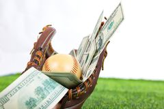 Close up of  baseball in a Glove with dollar bills in concept of Royalty Free Stock Photos