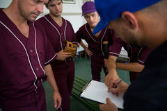 Close up of baseball team planning with coach. While standing at locker room royalty free stock photos