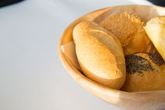 Close up of basket of various fresh bread rolls and buns on whit. E table. Space for text stock images