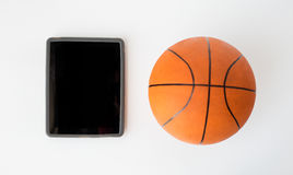 Close up of basketball ball and tablet pc computer Royalty Free Stock Photos