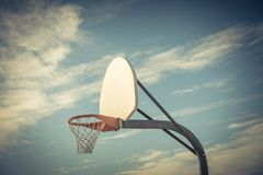 Close-up basketball hoop rim and backboard under cloud blue sky. Close-up a basketball hoop in public arena at community park in Irving, Texas, USA. Side view of Royalty Free Stock Photo