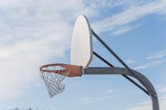 Close-up basketball hoop rim and backboard under cloud blue sky. Close-up a basketball hoop in public arena at community park in Irving, Texas, USA. Side view of Stock Photos