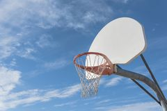 Close-up basketball hoop rim and backboard under cloud blue sky. Close-up a basketball hoop in public arena at community park in Irving, Texas, USA. Side view of Stock Photography