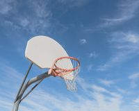 Close-up basketball hoop rim and backboard under cloud blue sky. Close-up a basketball hoop in public arena at community park in Irving, Texas, USA. Side view of Stock Photo