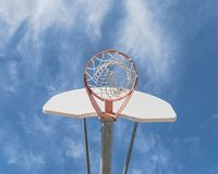 Close-up basketball hoop rim and backboard under cloud blue sky. Upward view a basketball hoop in public arena at community park in Irving, Texas, USA. Lookup of Stock Image