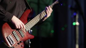 Close Up of bass guitarist playing on red rock bass guitar on the rock concert. Close Up of bass guitarist playing on red rock bass guitar on the rock concert stock footage