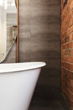Close up of bath end against grey tiled wall background Stock Image