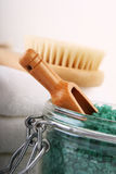 Close-up of bath salts, towels and brush. Close-up of bath salts with wooden scoop and towels and wooden brush in background - suggests pampering and relaxation Royalty Free Stock Photos