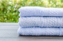 Close up of bath towels on wooden table with light bokeh Royalty Free Stock Photo