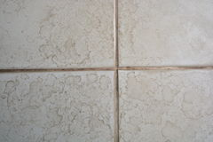 Close up of bathroom floor. Tile texture with water stain spot Royalty Free Stock Photo