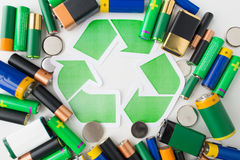 Close up of batteries and green recycling symbol Stock Photography