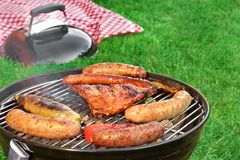 Close-Up Of BBQ Grill And Picnic Blanket In The Background. Close-Up Of BBQ Grill And Picnic Blanket In  Background On The Lawn. Summer Cookout Scene And Concept Royalty Free Stock Photos