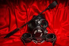 Close up bdsm outfit. Bondage, kinky adult sex games, kink and BDSM lifestyle concept. With gas mask, whip, collar, leather handcuffs on red silk with copy stock images