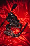 Close up bdsm outfit. Bondage, kinky adult sex games, kink and BDSM lifestyle concept. With gas mask, whip, collar, leather handcuffs , lash on red silk with royalty free stock image