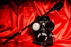 Close up bdsm outfit. Bondage, kinky adult sex games, kink and BDSM lifestyle concept. With gas mask, whip, collar on red silk with copy space royalty free stock images