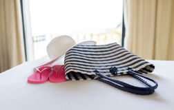 Close-up of beach bag, hat and flip-flop on bed Royalty Free Stock Photography
