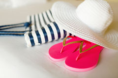 Close-up of beach bag, hat and flip-flops on bed Royalty Free Stock Photo
