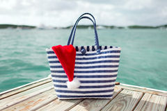 Close up of beach bag and santa helper hat Royalty Free Stock Images