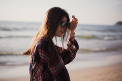 Close up beach portrait of cheerful blonde hipster. Wild girl on summer beach with sunglasses, hipster girl style Royalty Free Stock Image