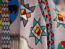 Close Up of Beaded Pow Wow Garments. Close up of beaded shawls and belts with geometric patterns and fringe worn at a pow wow stock photo
