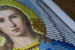 Close-up of the beadwork of the icon of Jesus Christ in a soft blurred background. Handwork. stock photos