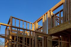 Close-up of beam built home under construction and blue sky with wooden truss, post and beam framework. Timber frame house, real royalty free stock photography