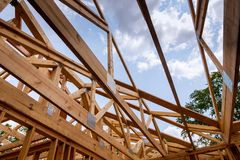 Close-up of beam built home under construction and blue sky with wooden truss, post and beam framework. Timber frame house, real stock photography