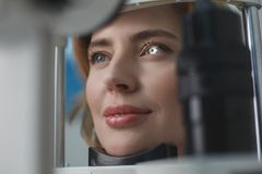 Glad female examining eyesight with equipment. Close up beaming woman face inspecting eyes in ophthalmological center. Medicine concept Stock Photo