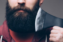 Close up of beard Confident young bearded man carrying a big axe. On shoulder and looking at camera while standing against grey background stock image