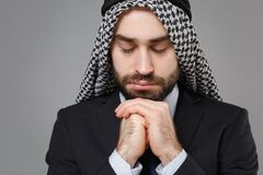 Close up of bearded arabian muslim businessman in keffiyeh kafiya ring igal agal classic suit isolated on gray