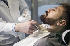 Close up of a bearded brown haired businessman sitting at a barber shop in a chair. stock photography