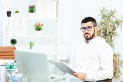Close up of a bearded businessman wearing glasses and sitting at his laptop and typing. There is a whiteboard and a. Bookcase in the background. in office Royalty Free Stock Photography