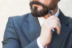 Close up of bearded chin hand holds glasses of businessman in suit and red tie. Businessman think over with hand near of his chin. stock photos