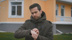 Close up of bearded man in brown coat standing in the street near orange and blue buildings checking his watch. Husband stock video