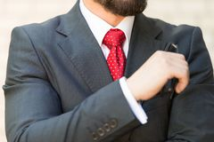 Close up of bearded man in elegant suit holding his glasses royalty free stock photo
