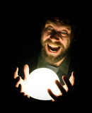Close-up of a bearded man expresses various emotions on a black background, holding a lamp in front of himsalf Royalty Free Stock Image