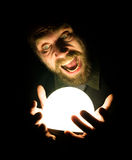 Close-up of a bearded man expresses various emotions on a black background, holding a lamp in front of himsalf Stock Images