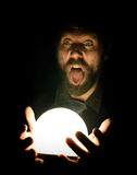 Close-up of a bearded man expresses various emotions on a black background, holding a lamp in front of himsalf Stock Photos