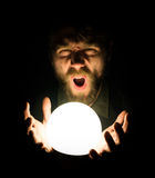 Close-up of a bearded man expresses various emotions on a black background, holding a lamp in front of himsalf Stock Image